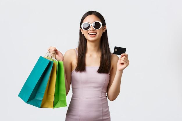 라이프 스타일, 쇼핑 및 관광 개념. 행복 한 화려한 아시아 여자 새 옷 가방을 들고 쇼핑몰에서 구입