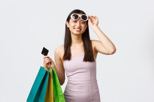 ライフスタイル、ショッピング、観光のコンセプト。ドレスとサングラス、笑顔のカメラで幸せなかわいいアジアの女性
