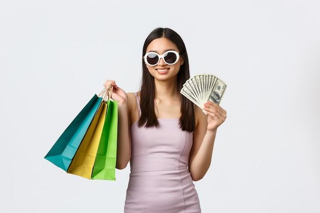 ライフスタイル、ショッピング、観光のコンセプト。金持ちの格好良いエレガントなアジアの女性、ドレスとサングラスを着用し、現金を示し、新しい服を買うのにお金を無駄にする