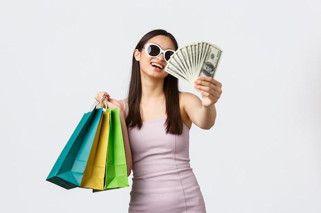 ライフスタイル、ショッピング、観光のコンセプト。ドレスとサングラスで裕福な若い韓国人女性を笑顔、のんきに笑って、服を買う