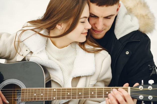 Lifestyle shot of couple sitting in snowy forest. people spending winter vacation outdoors. couple wit a guitar.