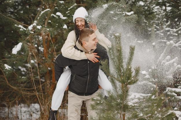 Colpo di stile di vita delle coppie che camminano nella foresta nevosa
