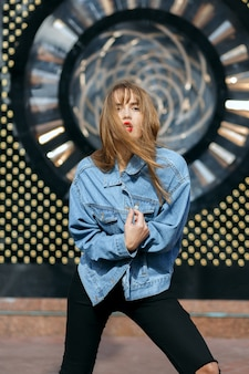 Lifestyle shot of glamor young woman with red lips wears jeans jacket