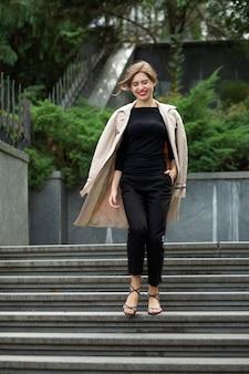 赤い唇と短い巻き毛の陽気な若い女性のライフスタイルショットは、階段を下りて行く流行の衣装を着ています