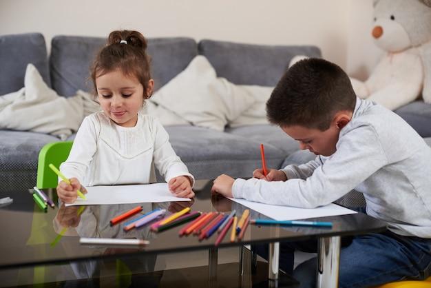 취학 전 아동 소녀와 테이블에 앉아서 그리기 모범생의 라이프 스타일 샷. 실내