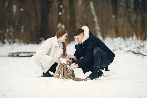 雪に覆われた森のカップルのライフスタイルショット。冬休みを屋外で過ごす人々。焚き火のそばの人々。