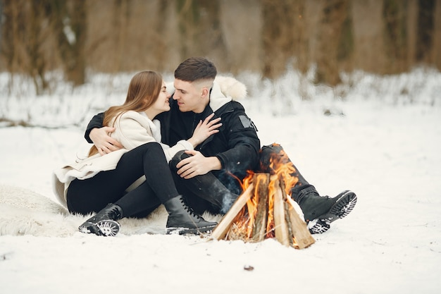 눈 덮인 숲에서 한 쌍의 라이프 스타일 샷입니다. 겨울 휴가를 야외에서 보내는 사람들. 모닥불 옆에있는 사람들.