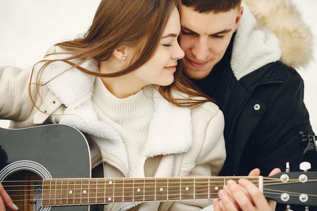 눈 덮인 숲에 앉아 부부의 라이프 스타일 샷. 겨울 휴가를 야외에서 보내는 사람들. 커플은 기타를 재치.
