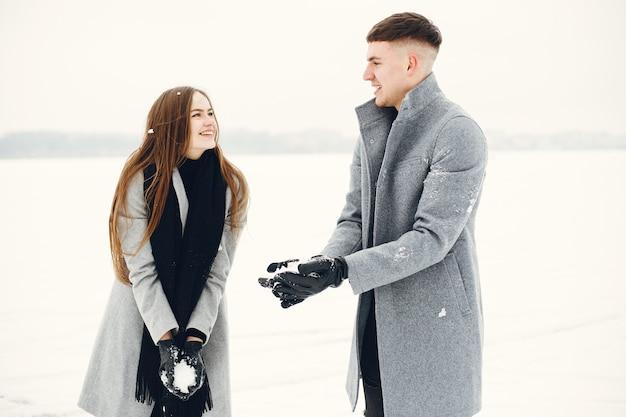 雪の森を歩くカップルのライフスタイルショット。冬休みを屋外で過ごす人々。