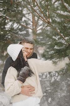 雪の森を歩くカップルのライフスタイルショット