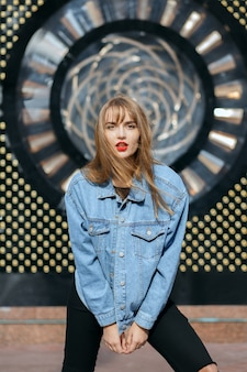 Lifestyle shot of wonderful young woman with red lips wears jeans jacket