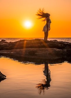 Lifestyle, silhouette of a young blonde on the coast on a sunset moving her hair, with the sun in the background