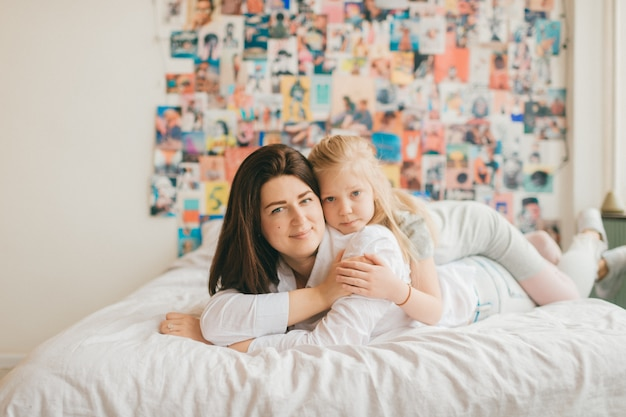 Lifestyle soft focus portrait of happy mom hugs her adorable daughter on white bed.