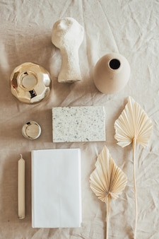 Lifestyle, still life composition with home decoration: book, fan leaves, granite brick, bust, candle, on beige linen table cloth
