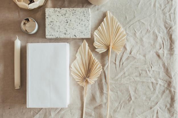 ライフスタイル、家の装飾と静物の構成:本、ファンの葉、花崗岩のレンガ、バスト、キャンドル、ベージュのリネンのテーブルクロス