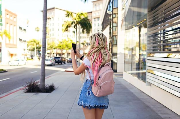 Lifestyle street fashion ritratto di donna bionda con i timori di scattare foto, stile casual hipster