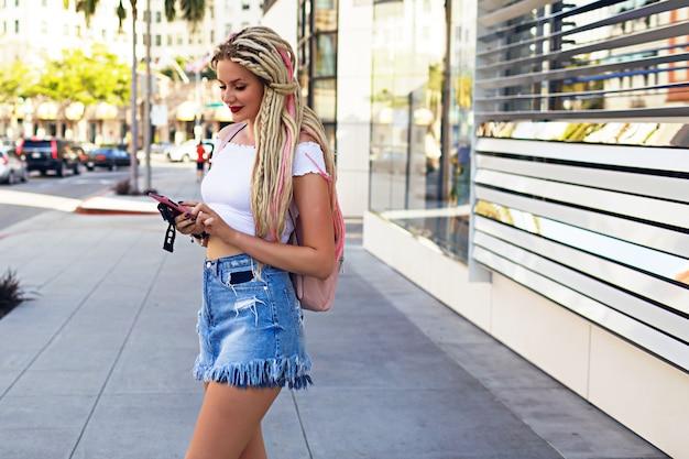 彼女のスマートフォン、カジュアルな流行に敏感なスタイルで恐怖のテキストメッセージで金髪の女性のライフスタイルストリートファッションポートレート
