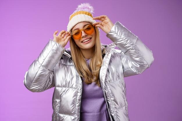 생활 양식. 세련된 팬티 대담한 금발 유럽 소녀 연기 멋진 착용 세련된 선글라스 실버 재킷 겨울 모자 확인 프레임 코 기울이기 머리 건방진 웃는 카메라 완벽한 여행 친구를 즐기고 있습니다.