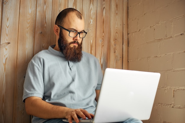 Lifestyle successful freelancer man with beard achieves new goal with laptop in loft interior