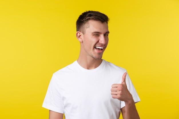 ライフスタイル、夏、人々の感情の概念。白いtシャツを着た生意気なハンサムな幸せな男、まばたきと親指を立てて、素敵な仕事を賞賛し、よくやった、達成を祝福します。