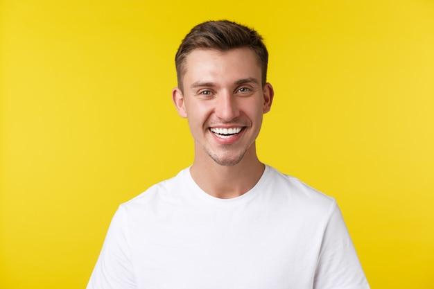 Концепция образа жизни, лета и людей эмоции. восторженная красивая мужская модель с счастливой улыбкой и белыми зубами, стоящая в повседневной футболке на желтом фоне, удовлетворена.
