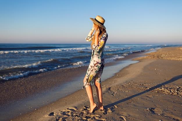 Stile di vita estate moda ritratto di bellezza donna bionda in posa sulla spiaggia solitaria, indossando bikini elegante pareo e cappello, guarda l'oceano, l'umore delle vacanze di lusso, colori dai toni luminosi.