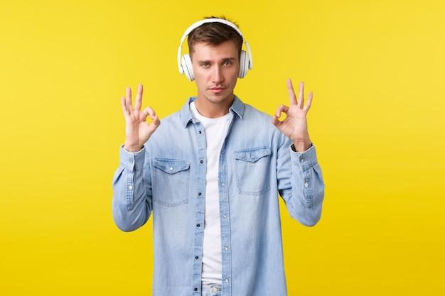 Stile di vita, vacanze estive, concetto di tecnologia. un bell'uomo biondo in abito casual, che mostra un gesto ok, come una fantastica nuova canzone o cuffie che ha comprato in vendita, sfondo giallo.
