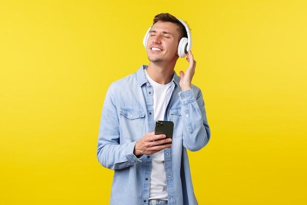 라이프 스타일, 여름 휴가, 기술 개념입니다. 캐주얼한 옷을 입고 웃고 있는 행복한 금발 남자, 눈을 감고 멋진 신곡 비트를 즐기고, 헤드폰으로 음악을 듣고, 휴대 전화를 사용합니다.