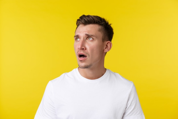 Lifestyle, summer and people emotions concept. close-up portrait of disappointed sad and tired young man in white t-shirt, looking upper left corner, gasping and frowning upset over bad news.
