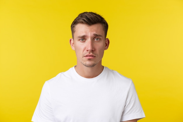 Lifestyle, summer and people emotions concept. close-up portrait of miserable distressed young man looking gloomy and sad, feeling heartbroken or tired, frowning over yellow background