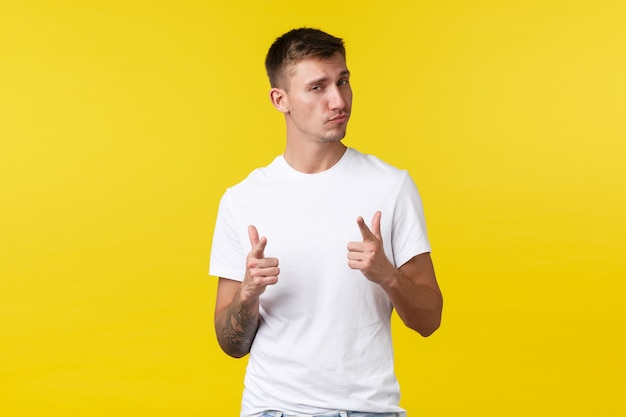 Lifestyle, summer and people emotions concept. pleased and impressed handsome man congratulate you, look proud, pointing at camera saying well played, nice work, yellow background.