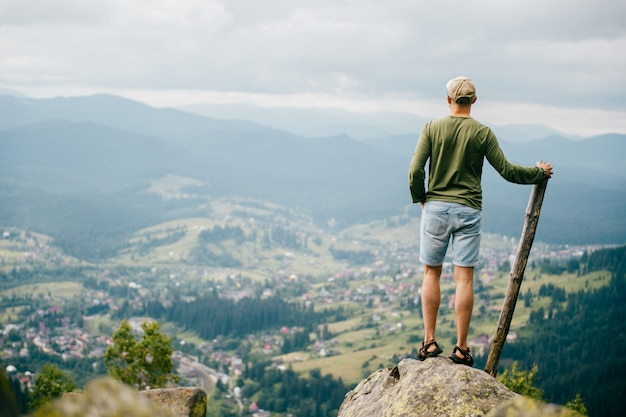 Lifestyle summer portrait from behind of successful man with wooden stick standing on top of mountaing with beautiful landscape in front.