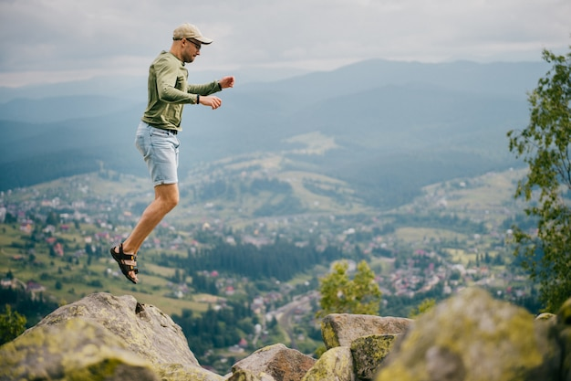 아름 다운 풍경 앞에 mountaing 위에 돌에서 점프하는 낚시를 좋아하는 남자의 라이프 스타일 여름 초상화.