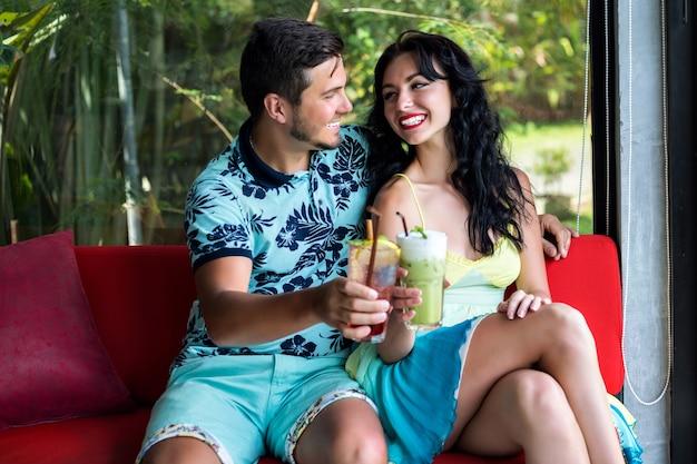 若い男性と女性のライフスタイルの夏の肖像画は、スタイリッシュなカフェでポーズをとって、カクテルを飲みながら、ロマンチックなデートを楽しんでいます