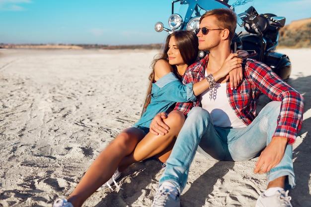 バイク-旅行の概念によって砂浜に一緒に座っている若いカップルライダーのライフスタイルの日当たりの良い肖像画。二人と自転車。ファッションの女性とハグと笑顔の男。