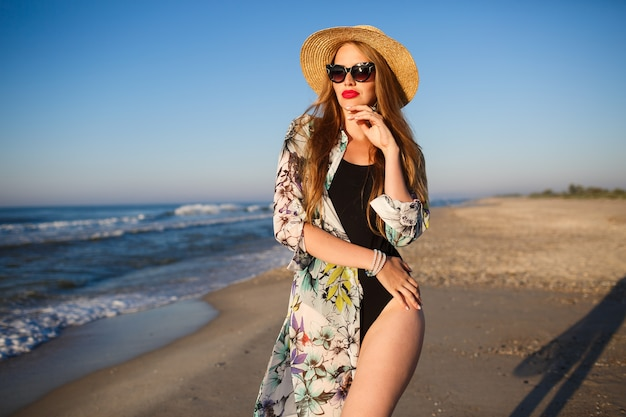 Lifestyle sunny portrait of young beauty photographer woman posing near lonely beach in the front of the ocean stylish bikini hat sunglasses and pareo, luxury vacation vibes.