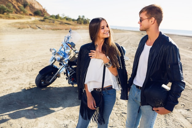 Lifestyle sunny portrait of young couple riders posing together on beach by motorbike - travel concept. two people and bike .fashion image of amazing sexy woman and man talk and laughing.