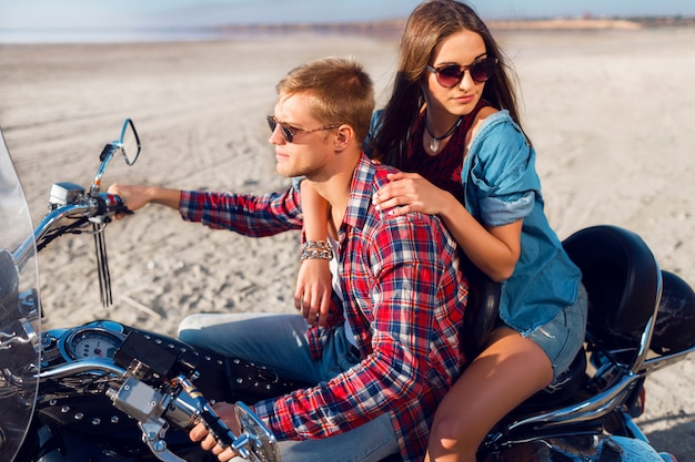Lifestyle sunny portrait of young couple riders sitting together on sand beach by motorbike - travel concept. two people and bike .fashion woman and man hugging and smiling.