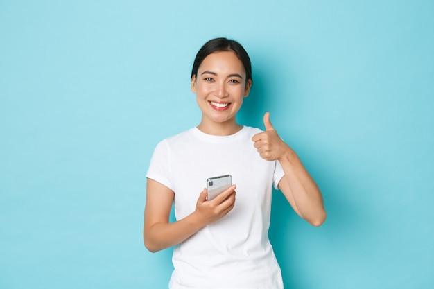 ライフスタイル、テクノロジー、eコマースのコンセプト。オンラインショップのクライアントである美しいアジアの女性の顧客に満足し、肯定的なフィードバックを残し、スマートフォンを持ち、親指を立てるジェスチャーを示します。