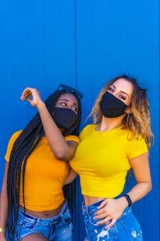 黄色のtシャツを着た青い壁にフェイスマスクを付けたライフスタイルの10代のガールフレンド。長い三つ編みの黒人の女の子と金髪の白人の女の子。コロナウイルスのパンデミック、新しい正常