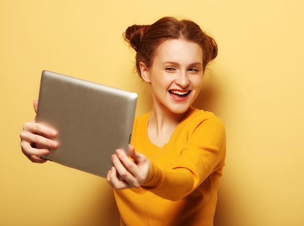ライフスタイル、技術、人々のコンセプト。黄色のデジタルタブレットで自分撮りをしている幸せな赤毛の女の子