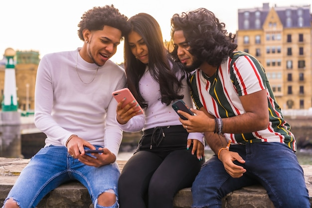 Lifestyle, three black friends having fun and watching social media on the street.