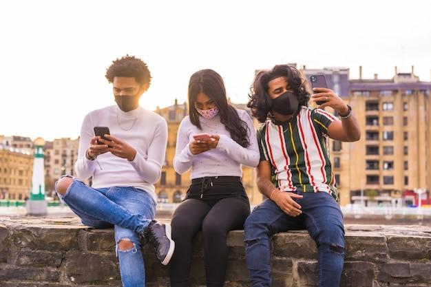 ライフスタイル、フェイスマスクを持って通りで携帯電話を見ている3人の友人