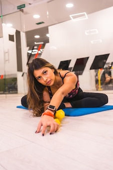 Lifestyle training in a gym, sport and health wellness. portrait of girl of hispanic ethnicity doing stretching