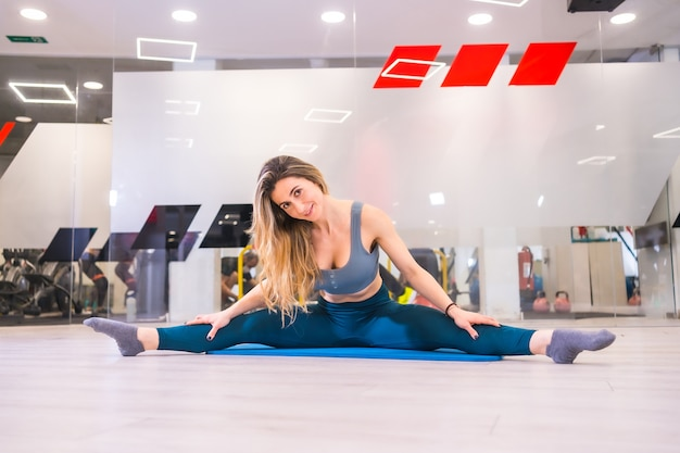 Lifestyle training in a gym, sport and health wellness. portrait of pretty blonde girl of caucasian ethnicity performing spaghetti