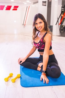 Lifestyle training in a gym, sport and health wellness. portrait of pretty brunette girl of hispanic ethnicity doing stretching