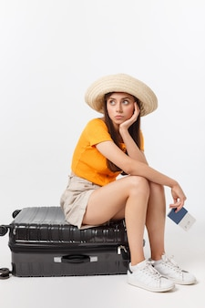 Lifestyle and travel concept: young beautiful caucasian woman is sitting on suitecase and waiting for her flight.isolated over white