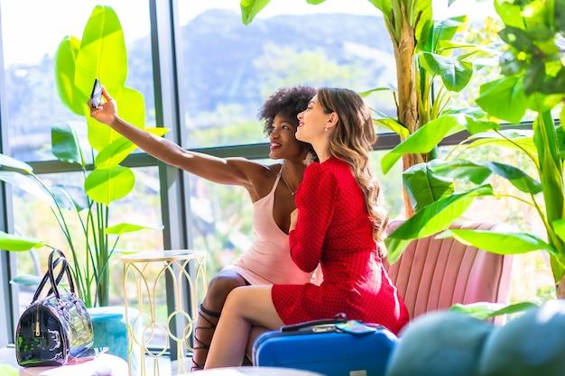 라이프 스타일, 모바일로 셀카를 찍는 여행 가방을 들고 호텔에 도착한 두 친구, 백인 금발 소녀와 아프로 헤어 스타일의 흑인 소녀, 분홍색 드레스와 빨간 드레스.