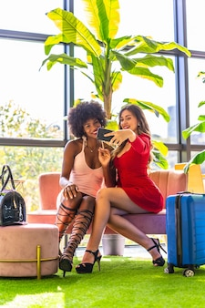 Lifestyle, two friends who have just arrived at the hotel with suitcases taking a selfie with the mobile, a caucasian blonde girl and a black girl with afro hair, a pink dress and a red dress.
