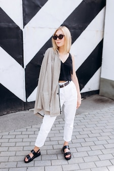 Lifestyle urban fashion trendy portrait of young cute blondie girl dressed in black and white clothes walking in the city in summer day in sun glasses